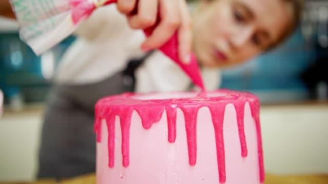 defekte konditorei mit gebäcksack, um handgemachte rosa schmetterlingskuchen mit tropfbeerenganache-frosting zu dekorieren, nahaufnahme absperrung schuss - zuckerguss stock-videos und b-roll-filmmaterial