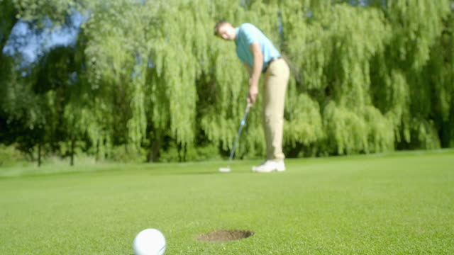 A De-Focused Golfer Putts on a beautiful green and misses