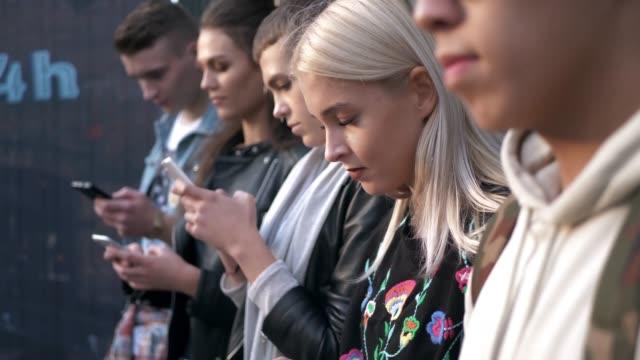 oskärpa grupp av studerande med mobiltelefon - missbruk koncept bildbanksvideor och videomaterial från bakom kulisserna