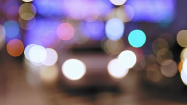 Defocused headlights and tail lights of cars in a city street at night
