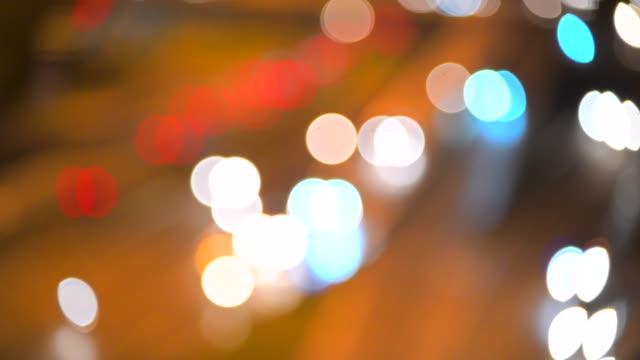 vídeos de stock e filmes b-roll de defocused lights street abstract . city blur background. moving bokeh circles of night traffic. - berma da estrada