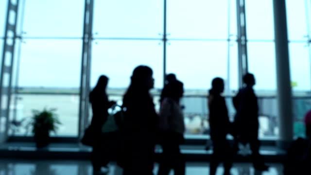 Defocused people walking in airport video