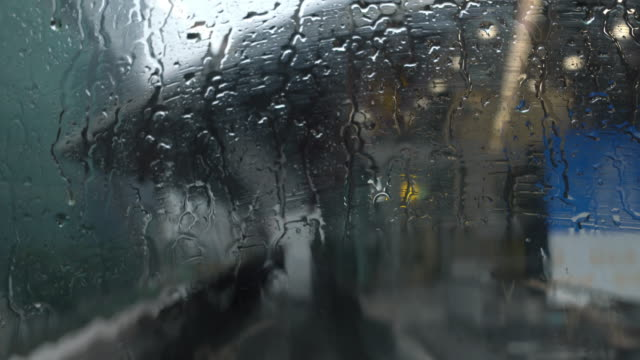 4K Defocused point of view of railway arriving to station in raining day seen through the train windshield during raindrops. Rain falling on railway window in rush hour working day.
