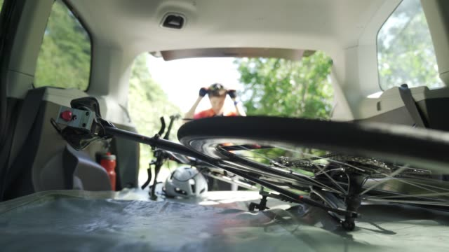 defocused professional cyclist taking down her bicycle from the car trunk ready to cycle - спортивное оборудование стоковые видео и кадры b-roll