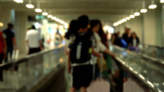 defocused shot of people on airport moving walkway - grandangolo tecnica fotografica video stock e b–roll