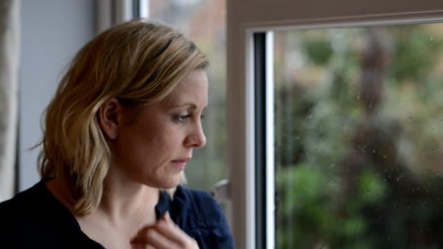 vídeos de stock, filmes e b-roll de desfocado tiro de mulher triste olhando pela janela - pena