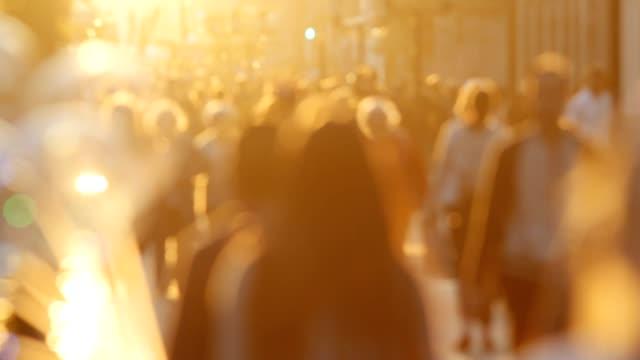 Defocused silhouette crowd of people walking down the street at summer sunset