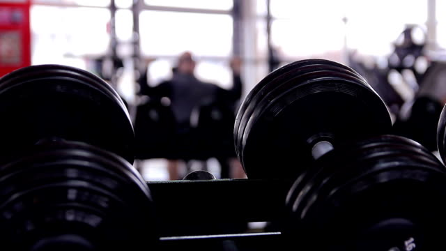 Defocused silhouette of male athlete doing bench press exercise in video