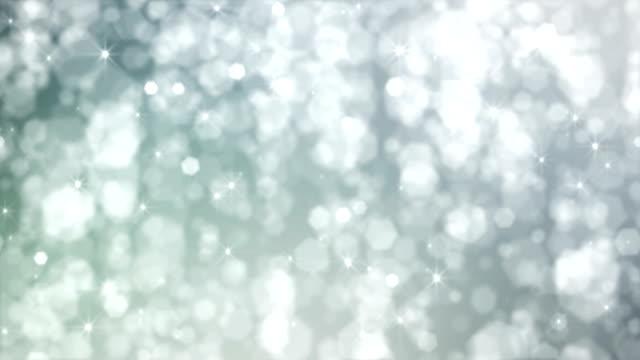 vídeos de stock, filmes e b-roll de estrelas de prata desfocadas e flocos de neve caindo do céu. loop - eventos de gala