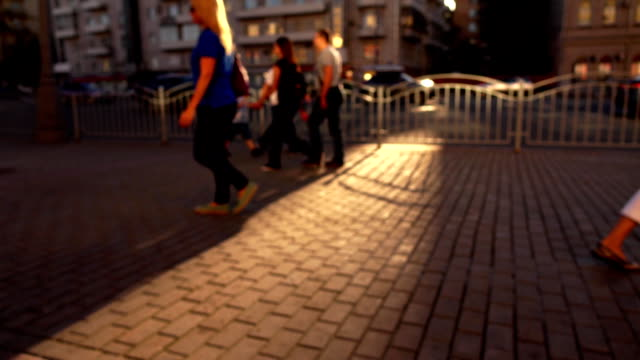 Defocused street in the evening. Cars and walking people. FullHD background bokeh wide shot video