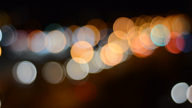 defocused street lights and car headlights crating a beautiful bokeh large colorful circles created by defocused streetlights and car headlights at night low lighting stock videos & royalty-free footage