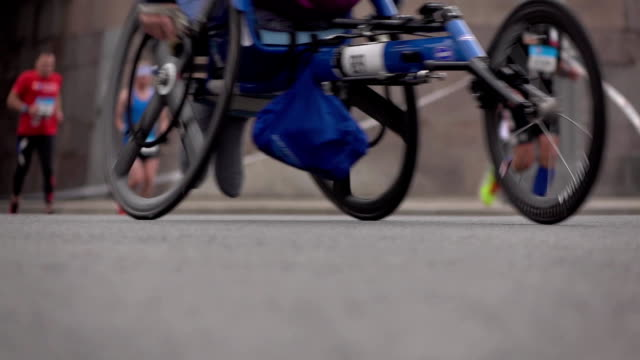Defocused wheelchair racer, runners and cyclists. Equal opportunities and competition concept. Slow motion background bokeh shot video
