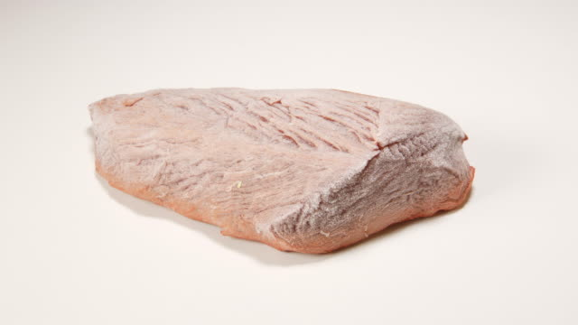 TIME-LAPSE: Defreezing a beef steak on white table TIME-LAPSE: Defreezing a beef steak on white table frozen stock videos & royalty-free footage
