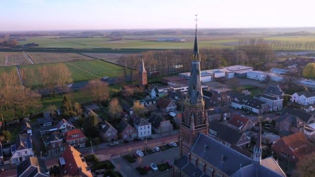 vídeos de stock, filmes e b-roll de um vôo de drone de 180 graus em torno de uma torre da igreja e uma vista na rodovia a59 com tráfego durante o nascer do sol em waalwijk, noord brabant, países baixos - sol nascente horizonte drone cidade