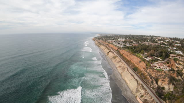 del mar california aerial view flying along coast above waterfront luxury homes and cliffside beach - klif filmów i materiałów b-roll