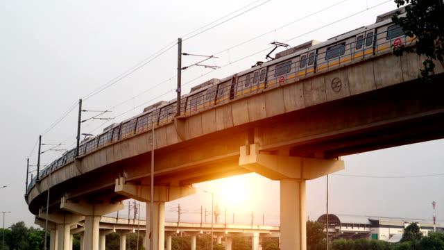 Delhi Metro Train passing over bridge during sunset time video