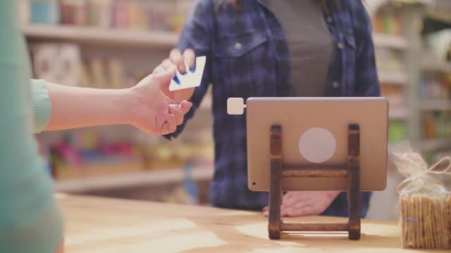 deli owner receiving payment through credit card from female customer - credit card filmów i materiałów b-roll