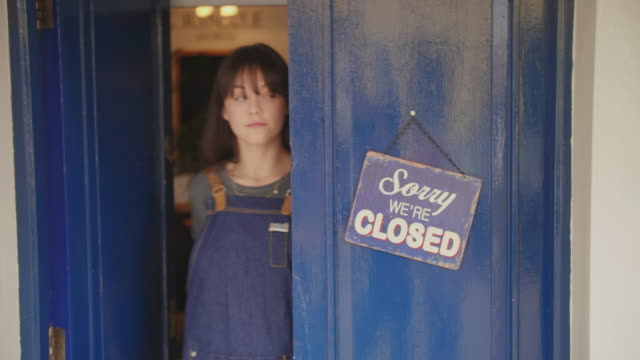Deli Owner Turning Sign From Closed To Open On Door video