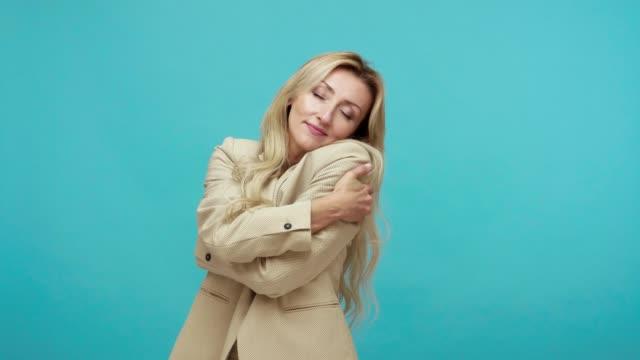 ビジネススタイルのスーツを着た繊細で脆弱な中年ブロンドの女性は、手で抱きしめ、なでを鳴らし、励まし、女性らしさを賞賛する - 支えられた点の映像素材/bロール