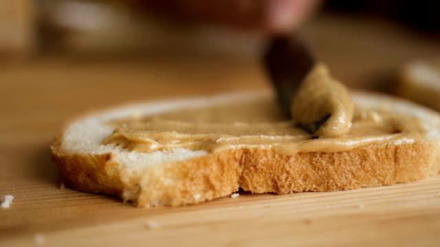 delicious and hearty breakfast nut cream on a crisp bread. man makes a peanut butter sandwich.. closeup of male hands spreading butter on bread in kitchen,  slow motion. - łyżka sztućce filmów i materiałów b-roll