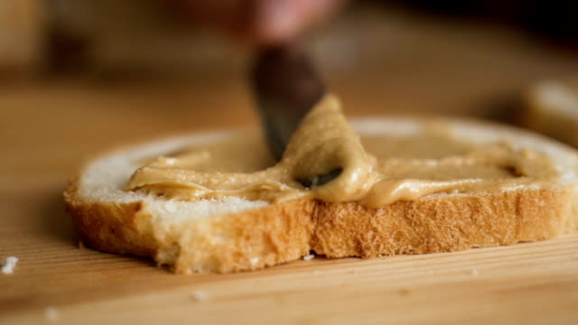 vídeos y material grabado en eventos de stock de deliciosa y abundante crema de nueces de desayuno sobre un pan crujiente. el hombre hace un sándwich de mantequilla de maní.. primer plano de las manos masculinas esparciendo mantequilla sobre el pan en la cocina, cámara lenta. - alergias alimentarias