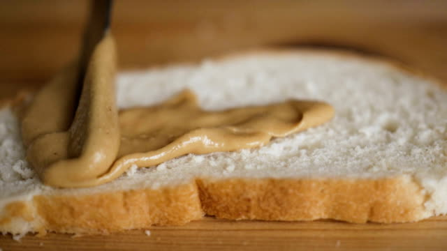 Delicious and hearty breakfast nut cream on a crisp bread. Man makes a peanut butter sandwich.. Closeup of male hands spreading butter on bread in kitchen,  slow motion. video
