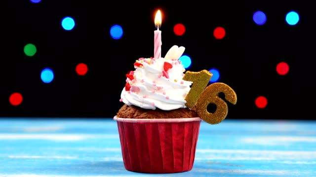 Delicious birthday cupcake with burning candle and number 16 on multicolored blurred lights background