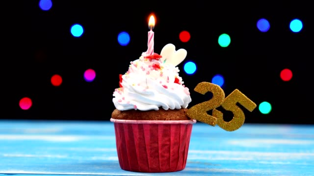 Delicious birthday cupcake with burning candle and number 25 on multicolored blurred lights background