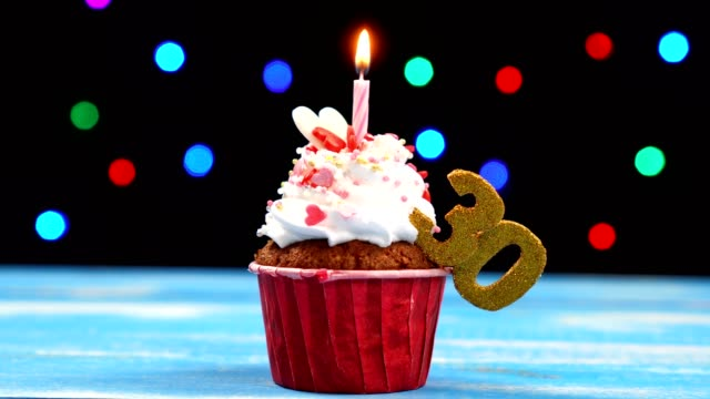 Delicious birthday cupcake with burning candle and number 30 on multicolored blurred lights background
