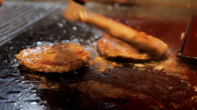 vídeos de stock e filmes b-roll de delicious burger patty flipped on hot pan. cooking meat for burger. cooking process, close up. preparing hamburger at the street food festival. fat meat frying on a grill - fast food