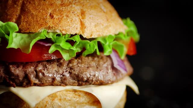un delizioso hamburger con tortino di manzo ruota sul tavolo. - hamburger video stock e b–roll
