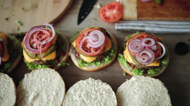 delicious burgers soon to be done - приготовление еды стоковые видео и кадры b-roll