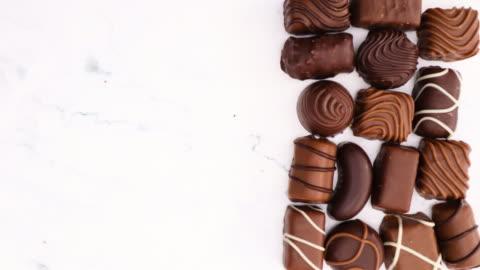 vídeos y material grabado en eventos de stock de deliciosos chocolates de varias formas sobre fondo de mármol - stop motion - postre