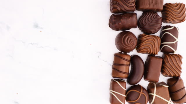 Delicious chocolates various shapes on marble background - Stop motion Delicious chocolates various shapes on marble background - Stop motion candy stock videos & royalty-free footage