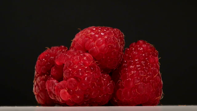 Delicious dessert of raspberries rotates on a gray background. Close up video