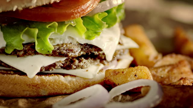 SLO MO DS Delicious double hamburger and crispy potato wedges Slow motion dolly close-up shot of a delicious double hamburger and crispy potato wedges. cheeseburger stock videos & royalty-free footage