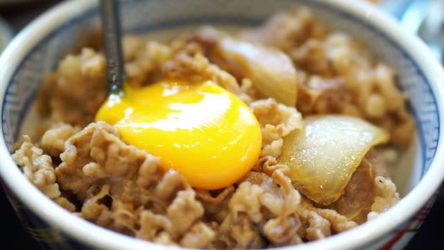 Delicious eating raw egg yolk on food beef over rice video