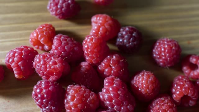 Delicious first class raspberries heap on wooden table