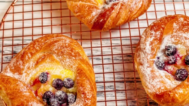Delicious fresh baked cheese danish pastries with powder sugar and blueberries on cooper cooling rack, close up top view