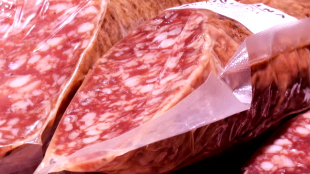 Delicious fresh salami sausages hang on the meat butcher market counter close up video