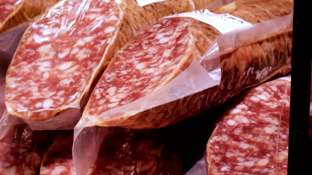 Delicious fresh salami sausages on the meat butcher market counter close up video