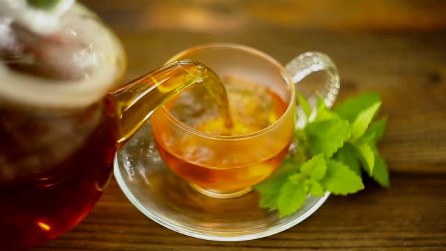 vidéos et rushes de thé vert délicieux dans un beau bol en verre sur la table - thé boisson chaude