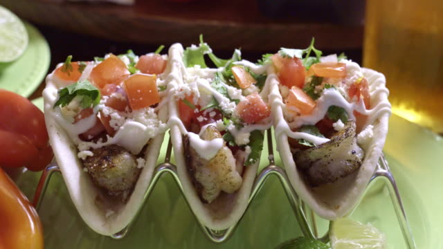 Delicious Grilled Shrimp Street Tacos Grilled shrimp street food tacos with lime garnish, sour cream, cilantro and onion and cotija cheese fish stock videos & royalty-free footage