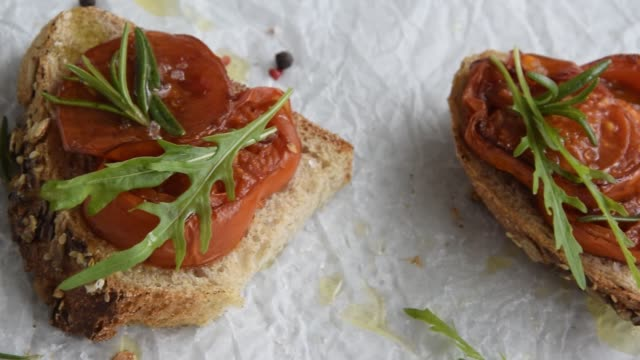 Delicious homemade bruschetta with whole grain bread, grilled tomatoes and fresh arugula. Vegetarian healthy snack, vegan food