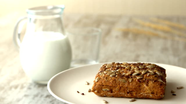 Delicious homemade small loaf of bread with seeds. Milk-jug, on wooden rustic table. Looped Tasly homemade brown bun with seeds. Milk-jug, on wooden rustic table. Looping 00266 loopable moving image stock videos & royalty-free footage