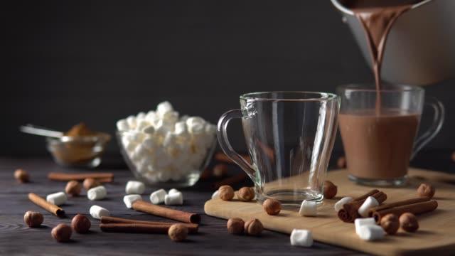vídeos de stock, filmes e b-roll de delicioso chocolate quente derramando em xícaras - chocolate quente