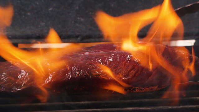 Delicious juicy meat steaks cooking on the grill on fire. Aged prime rare roast grilling tenderloin fresh juicy beef filet with lines slow motion. Grill, tasty beefsteak
