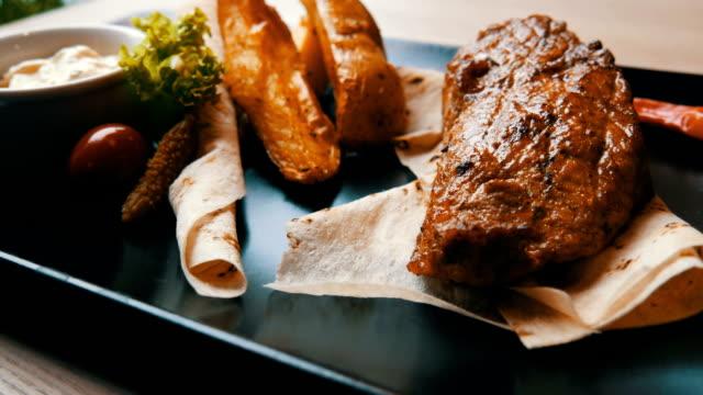 köstliches saftiges stück schweineschnitzel mit kartoffeln und gemüse auf einem stilvollen schwarzen teller im restaurant - portion stock-videos und b-roll-filmmaterial