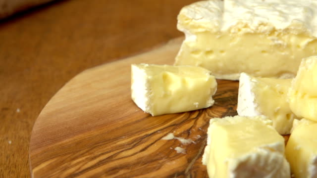 köstliches stück weicher brie-käse wird von einem holzbrett mit einer gabel genommen - brie stock-videos und b-roll-filmmaterial