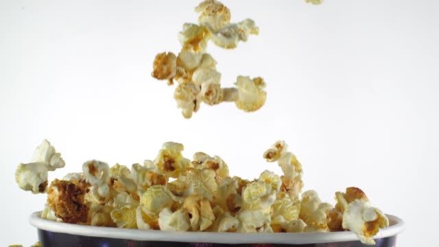vídeos de stock, filmes e b-roll de pipoca deliciosa que cai em uma caixa no movimento lento - balde pipoca